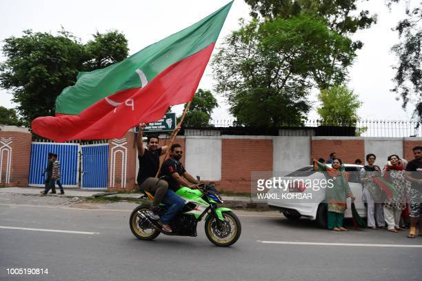 Supporters of Pakistani cricket star-turned-politician and head of the Pakistan Tehreek-e-Insaf Imran Khan ride on a bike along a street with a party...