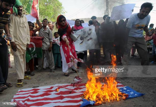 Supporters of Pakistani cricketer turned politician Imran Khan of Pakistan Tehreek-i-Insaaf torch a US flag during a demonstration against the...