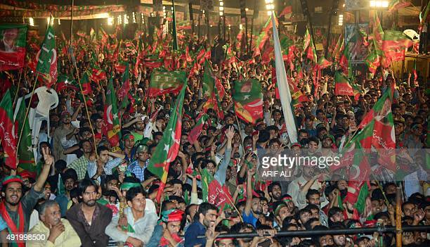 Supporters of Pakistani cricketer-turned-opposition leader Imran Khan wave flags of the Pakistan Tehreek-e-Insaf party, or Pakistan Movement for...