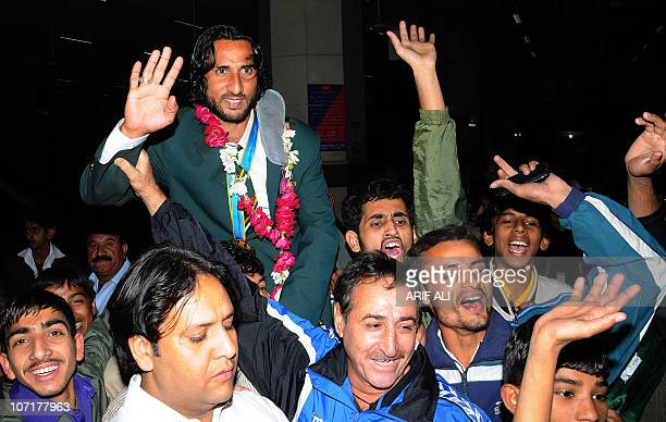 Supporters of Pakistani field hockey team carry player Shakeel Abbasi as he arrives from the Asian Games to Allam Iqbal International Airport in...