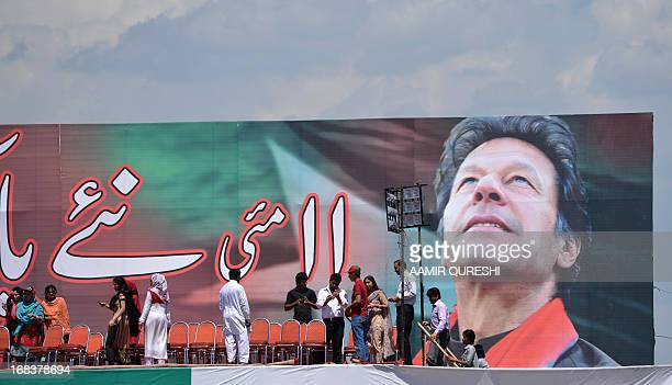 Supporters of Pakistani politician and former cricketer Imran Khan gather onstage beside a portrait of Khan at the venue of an election campaign...