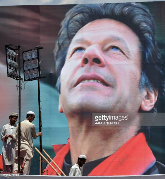 Supporters of Pakistani politician and former cricketer Imran Khan stand next to electoral poster of Khan at the venue of an election campaign...