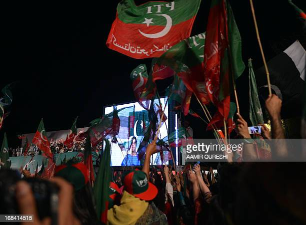 Supporters of Pakistani politician and former cricketer Imran Khan wave party flags as they listen to Khan on a screen through video link from a...