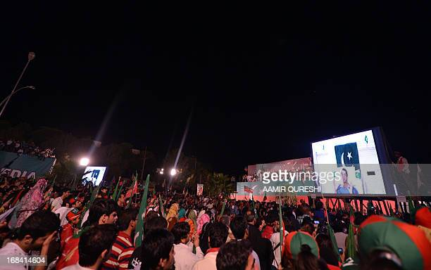 Supporters of Pakistani politician and former cricketer Imran Khan listen to Khan on a screen through video link from a hospital during the last...
