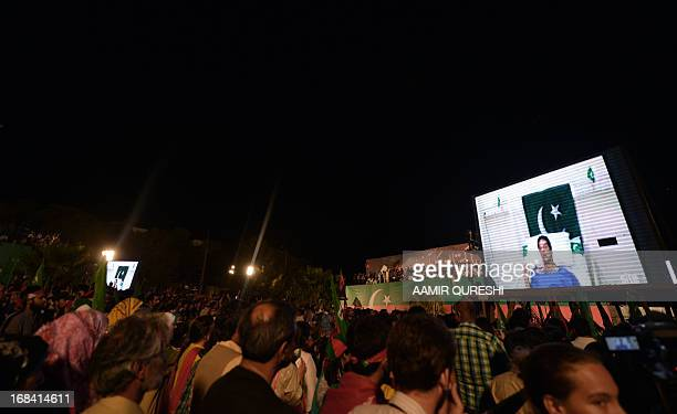 Supporters of Pakistani politician and former cricketer Imran Khan listen to Khan on the screens through video link from a hospital during the last...