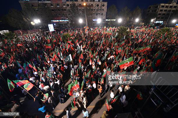 Supporters of Pakistani politician and former cricketer Imran Khan wave party flags as they wait to listen Khan video link address from a hospital...