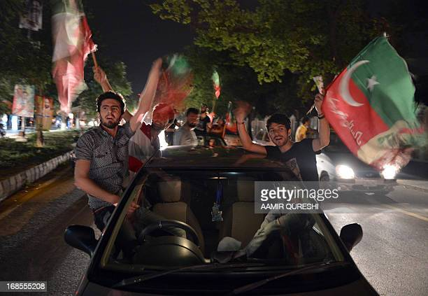 Supporters of Pakistani politician and former cricketer Imran Khan wave flags as they take part in a rally in Islamabad on May 11, 2013 after...