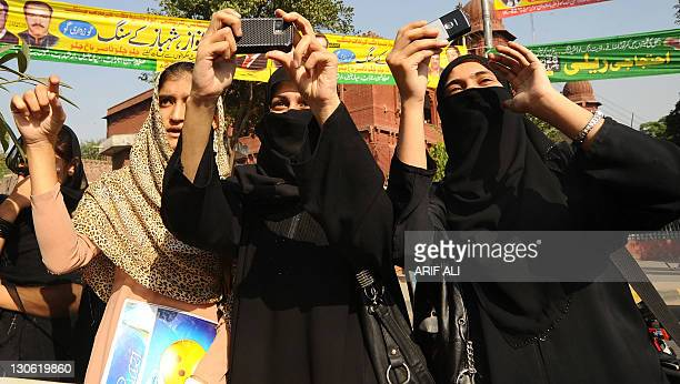 Supporters of Pakistani singer Abrarul Haq take his photograph as he leads a rally in Lahore on October 27 2011 Around 400 people joined the 'Save...
