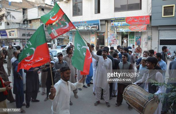 Supporters of Pakistan's cricketer-turned politician and head of the Pakistan Tehreek-e-Insaf Imran Khan, celebrates after Khan was elected by...