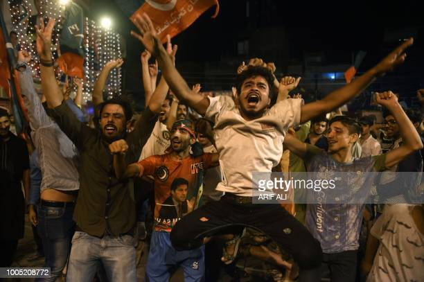Supporters of Pakistan's cricketer-turned politician Imran Khan, head of the Pakistan Tehreek-e-Insaf party, celebrate during general election in...