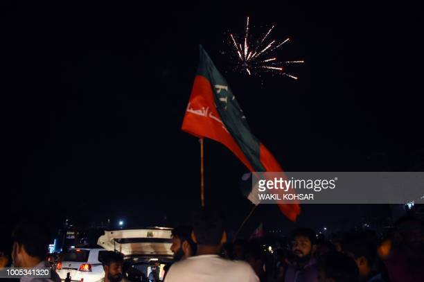 Supporters of Pakistan's cricketer-turned politician Imran Khan, head of the Pakistan Tehreek-e-Insaf party, cheer as fireworks go off as they...