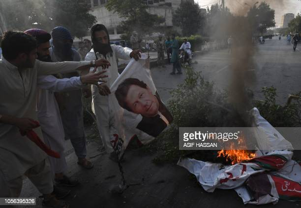 Supporters of Pakistan's religious hardline party Jamiat Ulema Islam torch a poster of Pakistan's Prime Minister Imran Khan on a block street during...