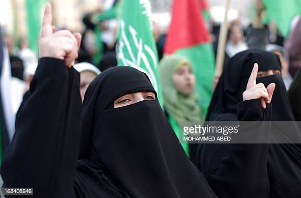 Supporters of Palestinian Islamic group Hamas raise up their fingers as they attend a festival of the International Association of Muslim Scholars...