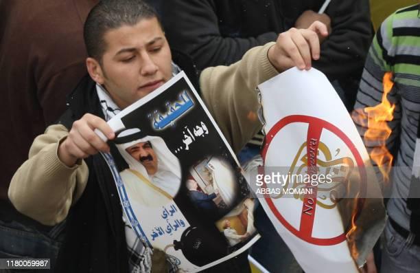Supporters of Palestinian president Mahmud Abbas burn the logo of Al-Jazeera news channel and a portrait of the Emir of Qatar Sheikh Hamad bin...