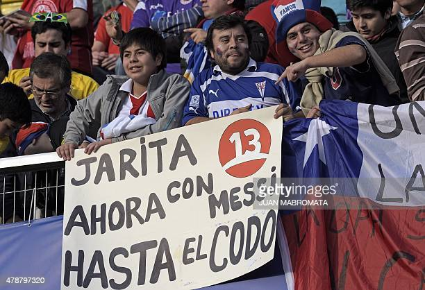 Supporters of Paraguay hold a sign reading Jarita now with Messi up to the elbow referring to Chilean player Gonzalo Jara's incident with Uruguayan...