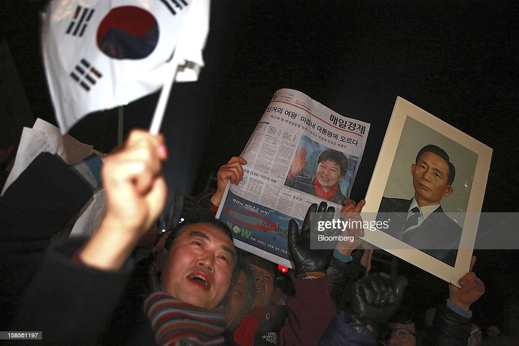 Supporters of Park Geun Hye, the president-elect from the ruling New Frontier Party, celebrate as they also hold a portrait of Park's father, the late president Park Chung Hee, at right, in Seoul, South Korea, on Thursday, Dec. 20, 2012. Park was elected president of South Korea, becoming the first woman to lead Asia's fourth- biggest economy more than 30 years after her father's reign as dictator ended with his assassination. Photographer: Jean Chung/Bloomberg via Getty Images
