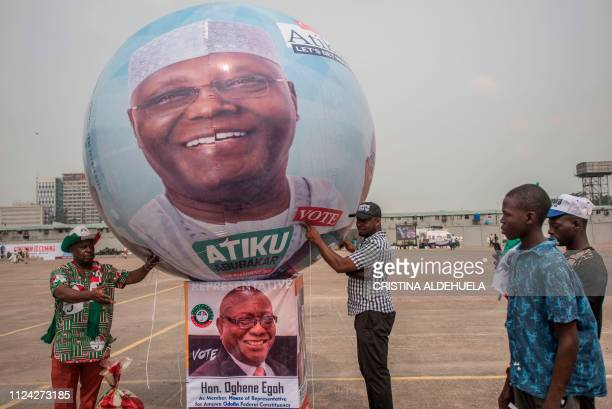 Supporters of People's Democratic Party hold a balloon bearing a portrait of People's Democratic Party presidential candidate for the forthcoming...
