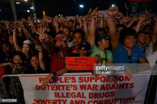 Supporters of Philippine President Rodrigo Duterte raise clinched fists during a rally at a park in Manila on February 25 coinciding with 'People...