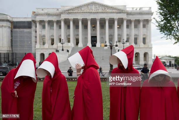 Supporters of Planned Parenthood dressed as characters from 'The Handmaid's Tale' hold a rally as they protest the US Senate Republicans' healthcare...