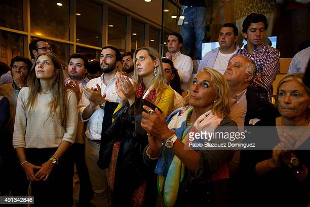 Supporters of Portuguese Prime Minister and Social Democratic Party's leader Pedro Passos Coelho applause him as they watch him on a tv screen after...