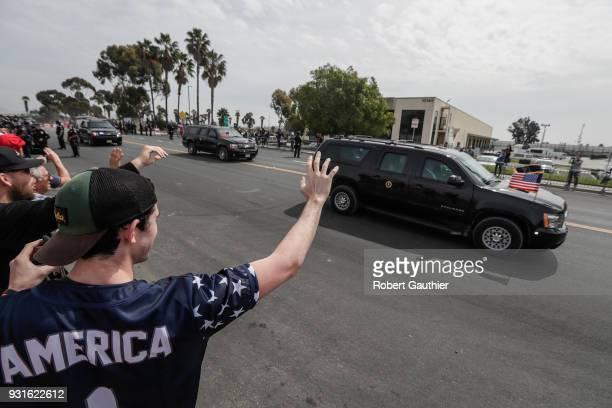 Supporters of President Donald J Trump wave at his motorcade as he travels along Via De La Amistad after viewing a collection of border wall...