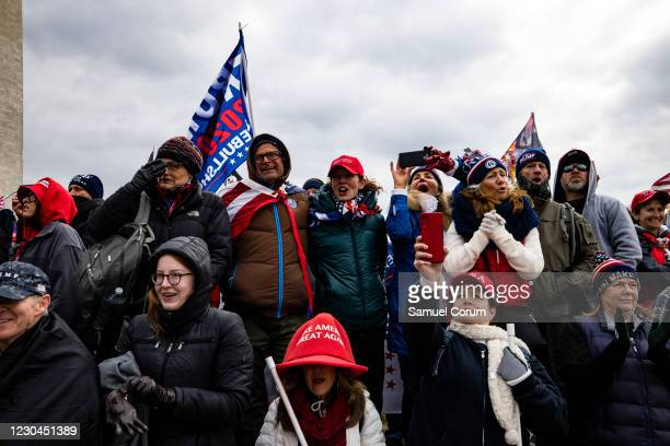 Supporters of President Donald Trump cheer as he appears on a screen during a rally on the National Mall on January 6, 2021 in Washington, DC. Trump...