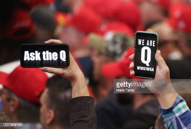 Supporters of President Donald Trump hold up their phones with messages referring to the QAnon conspiracy theory at a campaign rally at Las Vegas...