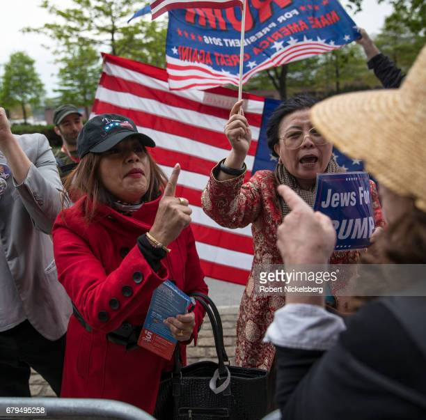 Supporters of President Donald Trump left and center argue with protesters before the arrival of the motorcade carrying President Donald Trump near...