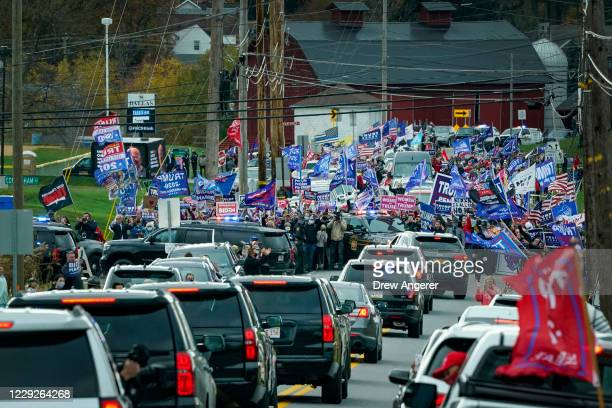 Supporters of President Donald Trump line the road as the motorcade for Democratic presidential nominee Joe Biden makes its way to a drive-in...