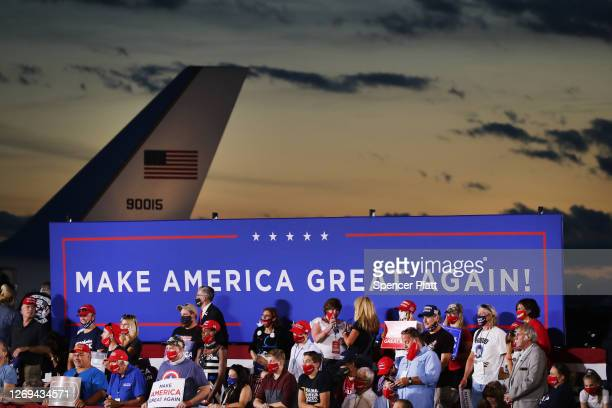 Supporters of President Donald Trump listen as he speaks at an airport hanger at a rally a day after he formally accepted his party's nomination at...