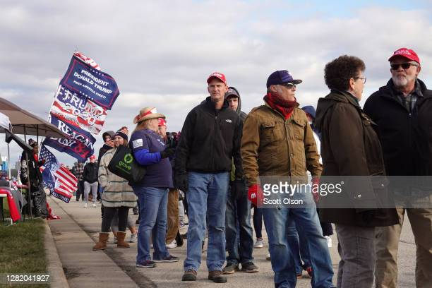 Supporters of President Donald Trump wait in line as they arrive for a campaign rally at the Waukesha County Airport on October 24, 2020 in Waukesha,...