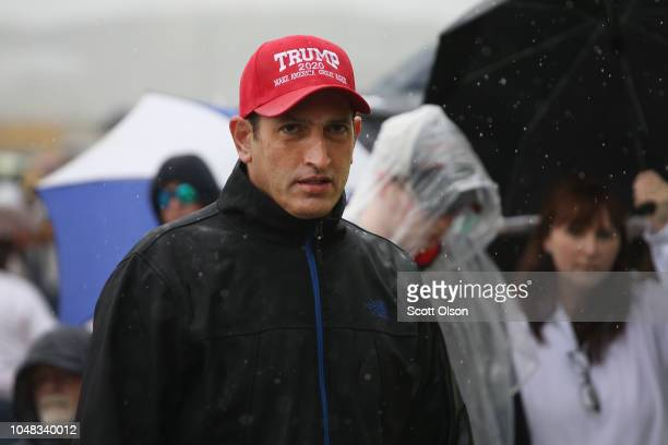 Supporters of President Donald Trump wait in line in the rain for the doors to open at the MidAmerica Center where the president is scheduled to...