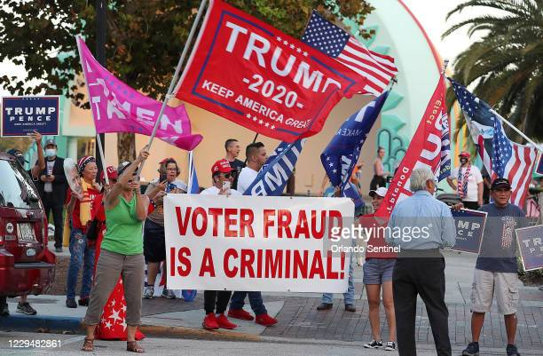 """Supporters of President Donald Trump wave flags and chant """"Stop the Cheat!"""" as they gather to rally at Lake Eola Park in Orlando, Florida,..."""