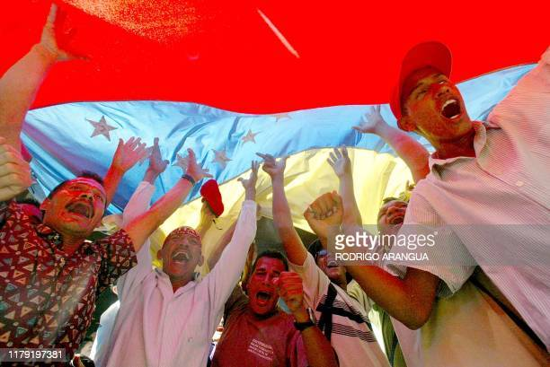 Supporters of President Hugo Chavez shout slogans under a Venezuelan flag in front of National Electoral Building in Caracas 08 January 2003...