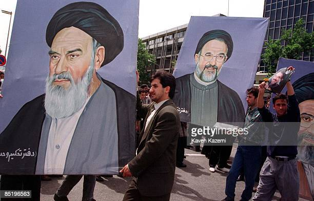 Supporters of president Mohammad Khatami carry a painting of him along with those of Ayatollah Khomeini and Ayatollah Khamenei on the first...