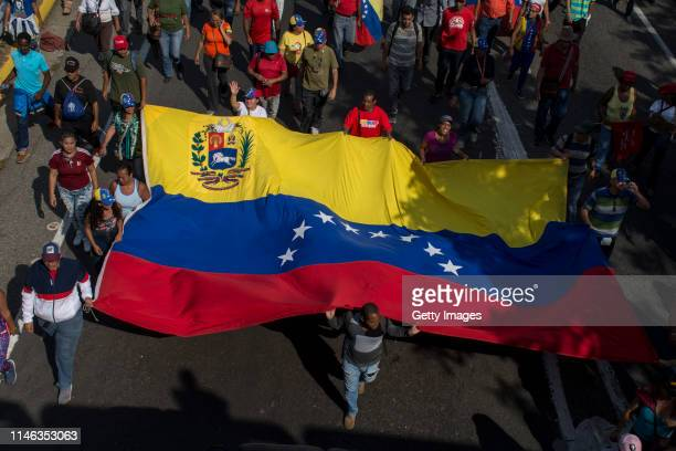 Supporters of president Nicolás Maduro carry a giant Venezuelan flag during a demonstration at ValleCoche freeway on May 01 2019 in Caracas Venezuela...