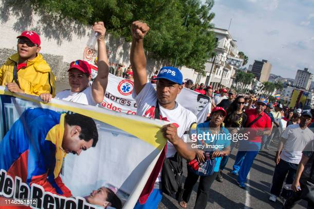 Supporters of president Nicolás Maduro hold banners during a demonstration on May 01 2019 in Caracas Venezuela Yesterday Venezuelan opposition leader...
