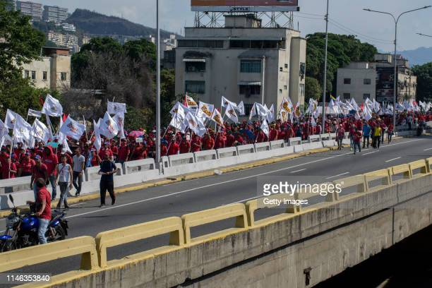 Supporters of president Nicolás Maduro march holding flags during a demonstration at ValleCoche freeway on May 01 2019 in Caracas Venezuela Yesterday...