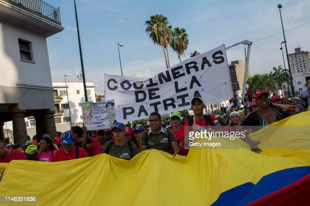 Supporters of president Nicolás Maduro march with a giant Venezuelan flag during a demonstration on May 01 2019 in Caracas Venezuela Yesterday...