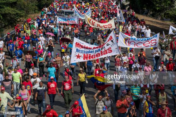 Supporters of president Nicolás Maduro march with banners during a demonstration at ValleCoche freeway on May 01 2019 in Caracas Venezuela Yesterday...