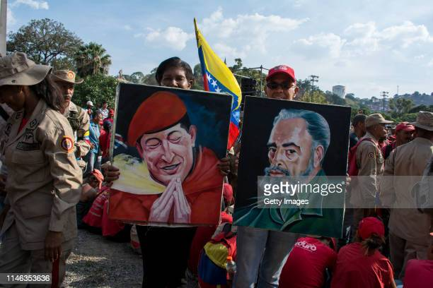 Supporters of president Nicolás Maduro show paintings of late former president of Venezuela Hugo Chávez and Cuba's late former president Fidel Castro...