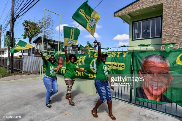 Supporters of presidential candidate David Granger of the National Unity and Alliance for Change party cheer and wave flags in front of their house...
