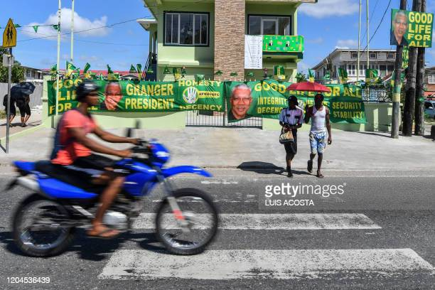 Supporters of presidential candidate David Granger of the National Unity and Alliance for Change party adorn their home with party banners in...