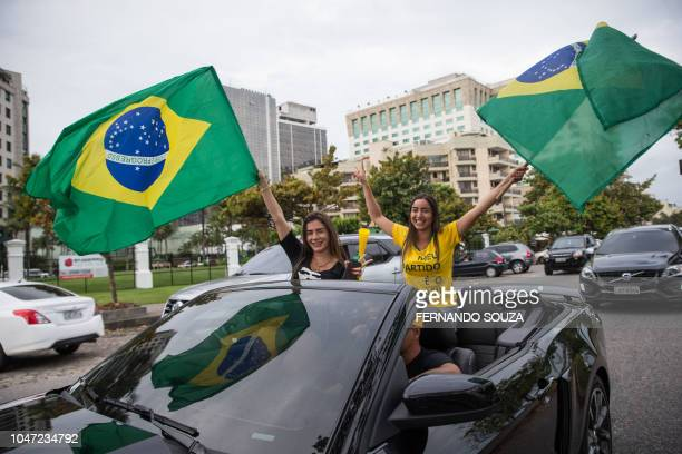 Supporters of presidential candidate for the Social Liberal Party Jair Bolsonaro cheer in front of the residential condominium where he lives in...