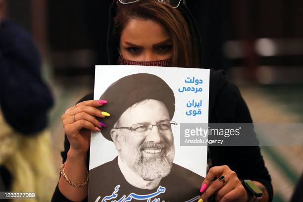 Supporters of presidential candidate Iranâs judiciary chief Ebrahim Raisi, holding banners and the photos of him gather during a rally ahead of the...