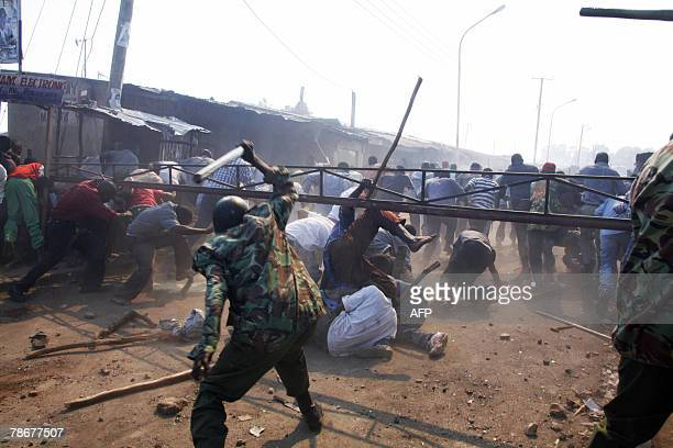 Supporters of presidential candidate Raila Odinga scramble away from a batton wielding Kenyan policeman after they set fire to some houses at the...