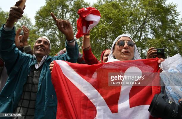 Supporters of Pro-Indian National Conference party dance as they attend an election campaign in Srinagar on April 15, 2019. - India's gargantuan...