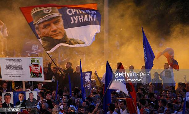 Supporters of Ratko Mladic wave flags with his picture and reading in Serbian 'Serbian hero' during a rally organized by the ultra nationalist...