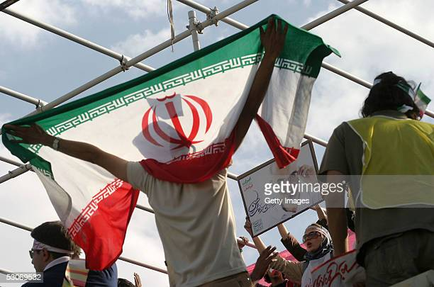 Supporters of reformist Iranian presidential candidate Mostafa Moin wave their national flag during a presidential rally on June 14 2005 in Tehran...
