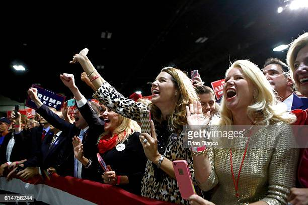 Supporters of Republican presidential candidate Donald Trump cheer as he arrives to speak at a rally on October 14 2016 at the Charlotte Convention...
